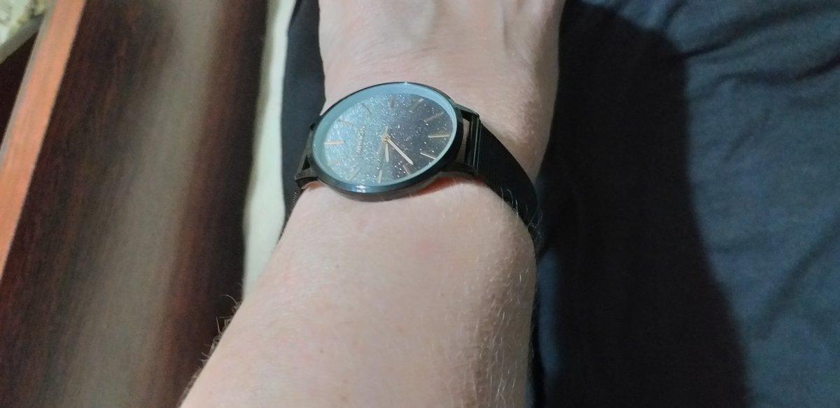 Часы черные, циферблат переливается на солнце.